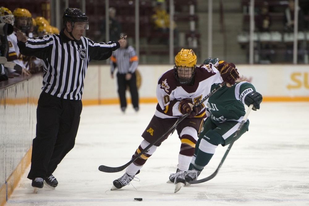 Sophomore forward Alex Woken maneuvers the puck away from a Bemidji State player at Ridder Arena on Friday, Dec. 1. The Gophers won 3-2 in overtime.