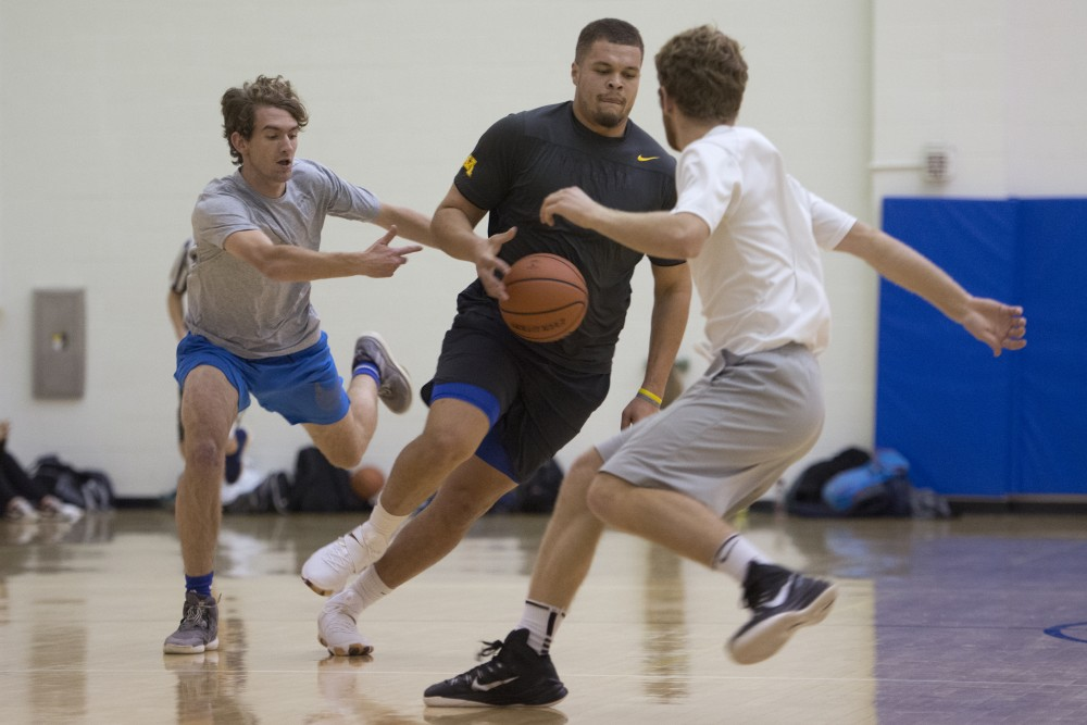Senior Noah Scarver handles the ball during an intramural game on Monday, Dec. 4 at the Rec Center on East Bank. Scarver previously played football for the Gophers.