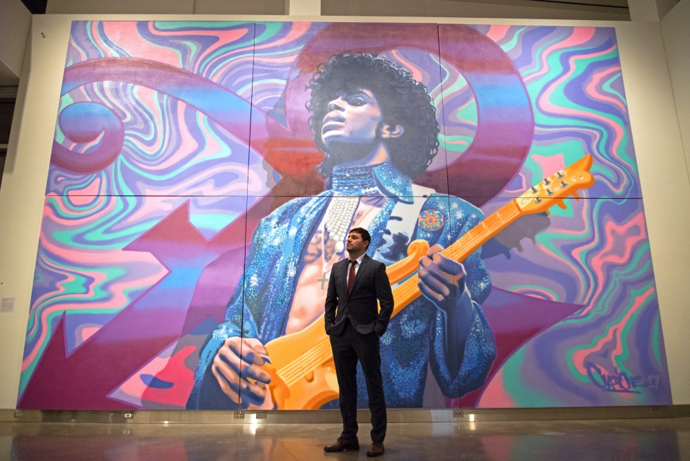 Aerosol artist Rock Martinez poses for a portrait with the mural he created in honor of Prince inside the Weisman Art Museum during the preview party for the