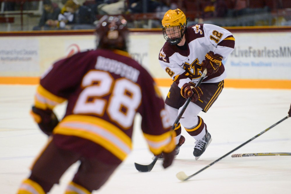 Grace Zumwinkle keeps the puck away from a Minnesota-Duluth player on Friday, Dec. 8 at Ridder Arena.