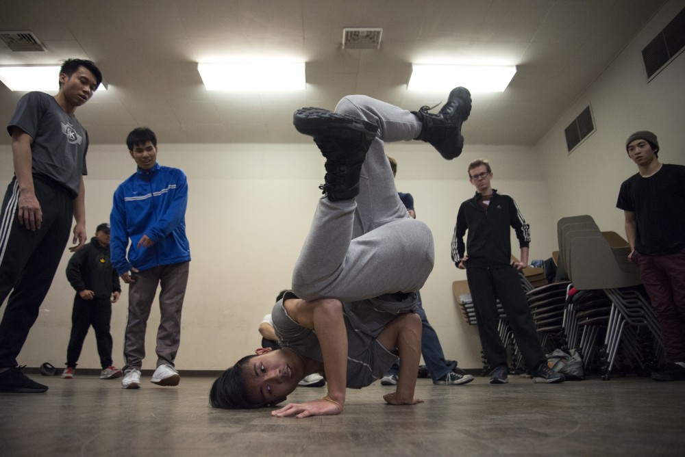 Seth Souvannayoung is cheered on by friends during a dance practice in Peik Gymnasium.