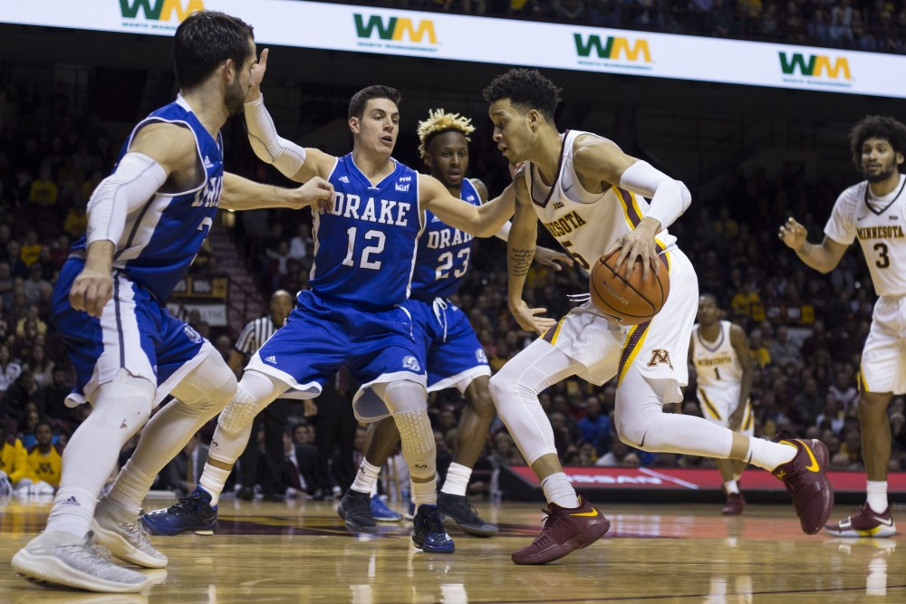 Sophomore guard Amir Coffey dribbles toward the hoop during the game against Drake on Monday, Dec. 11, 2017 at Williams Arena.