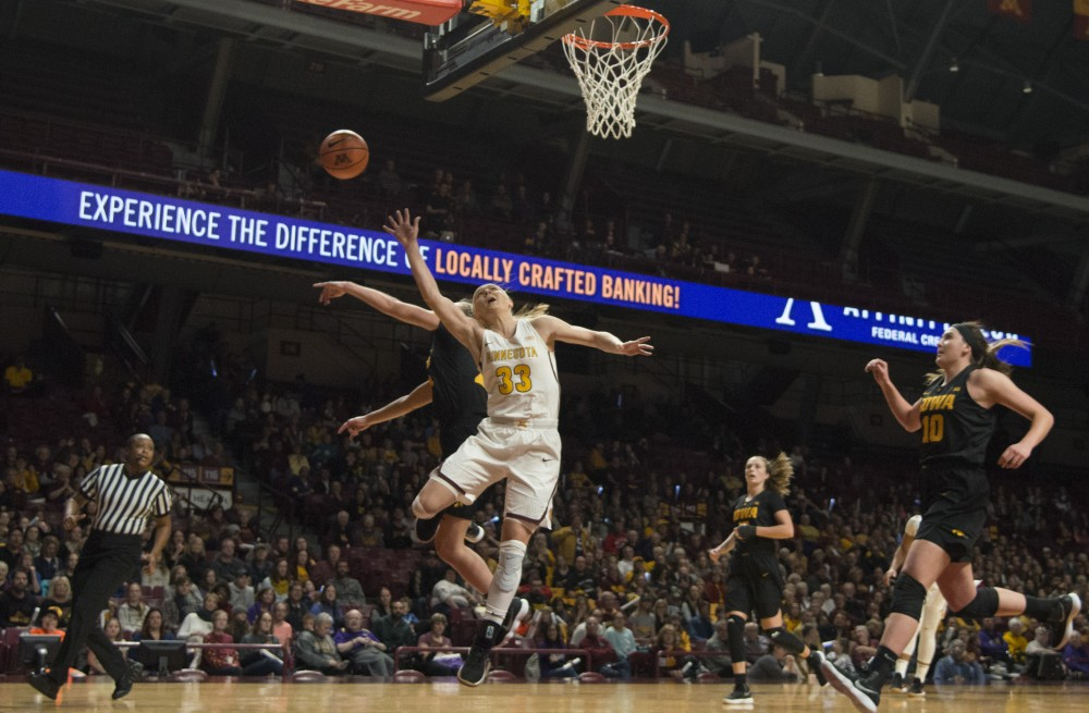 Senior guard Carlie Wagner blocks a shot by Iowa at Williams Arena on Sunday.