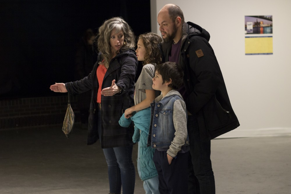 A family views Josh K. Winkler's piece at the Land Body Industry art exhibition at the Katherine E. Nash Gallery in Regis Center for Art on Saturday, January 20.