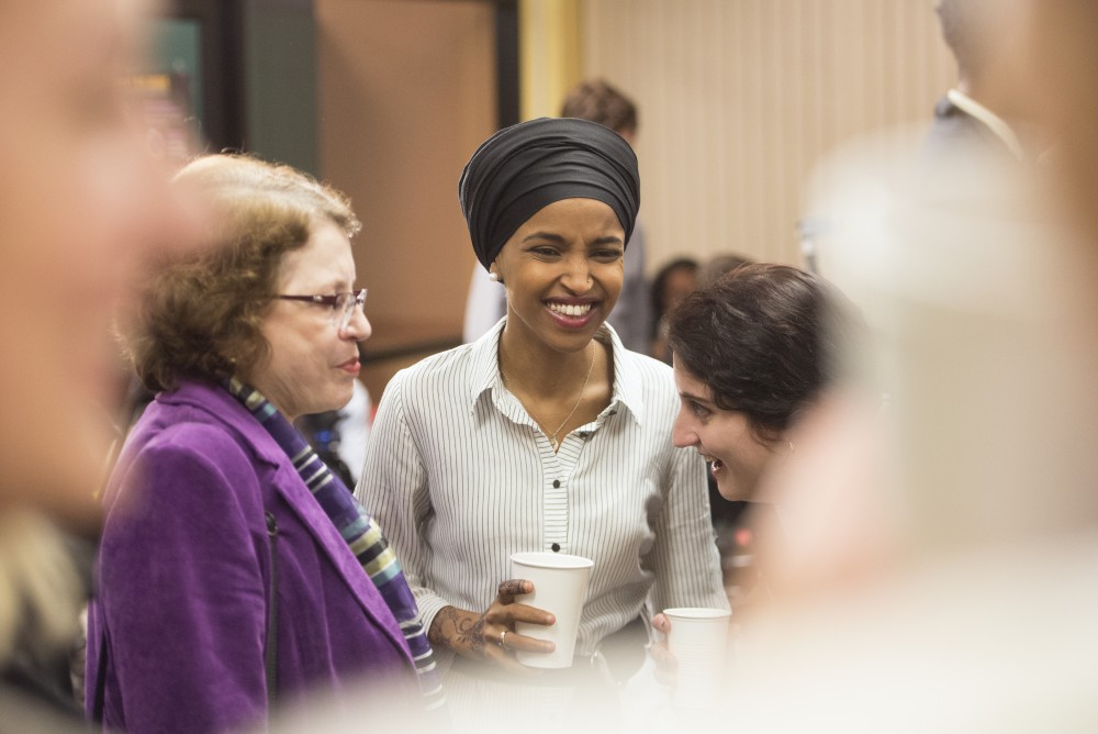 State Rep. Ilhan Omar talks with attendees before speaking at her campaign kickoff.
