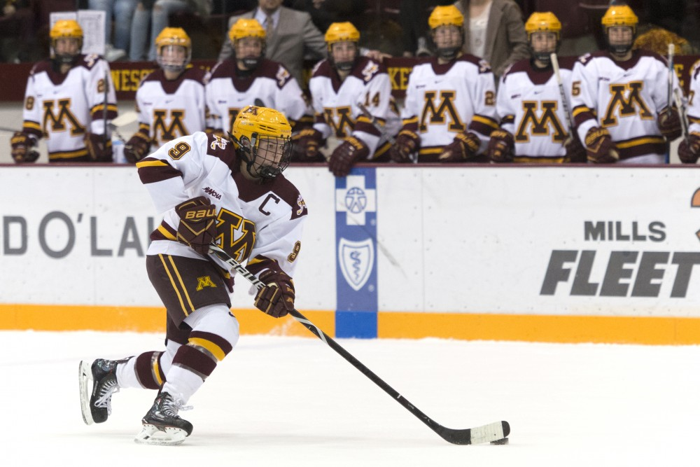 The Gopher women's hockey team watches on as senior defenseman Sydney Baldwin brings the puck down the ice on Dec. 1, 2017 at Ridder Arena.