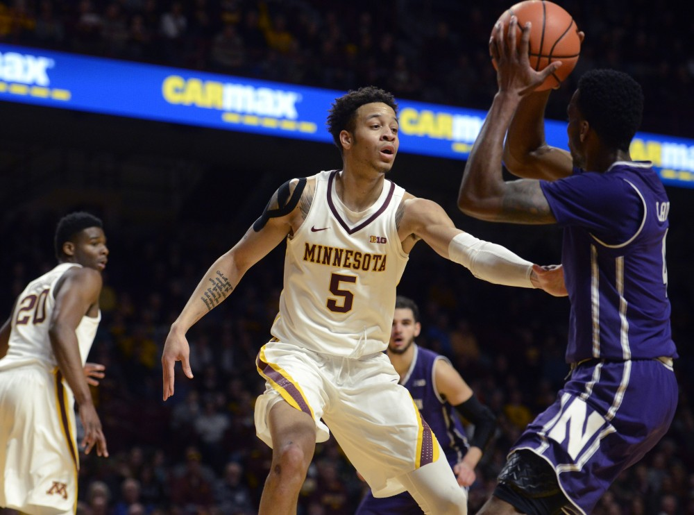 Sophomore guard Amir Coffey reaches out to block Northwestern forward Vick Law during a game at Williams Arena on Tuesday.