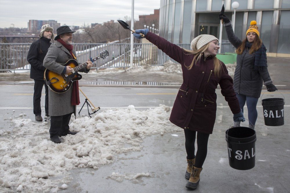 Communications professor Mark Pedelty performs harmonica with a band and University dance majors for a music video on Saturday, Jan. 20 on the Washington Avenue Bridge. The music video aims to communicate the effects of using salt during the winter to audiences like local business owners for his project Field to Media: Applied Musicology for a Changing Climate.