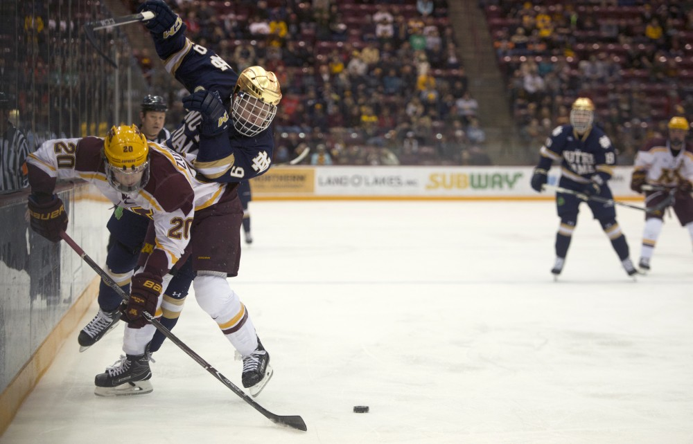 Sophomore defenseman Ryan Zuhlsdorf fights for the puck during a game against Notre Dame on Friday, Jan. 26 at 3M Arena at Mariucci.