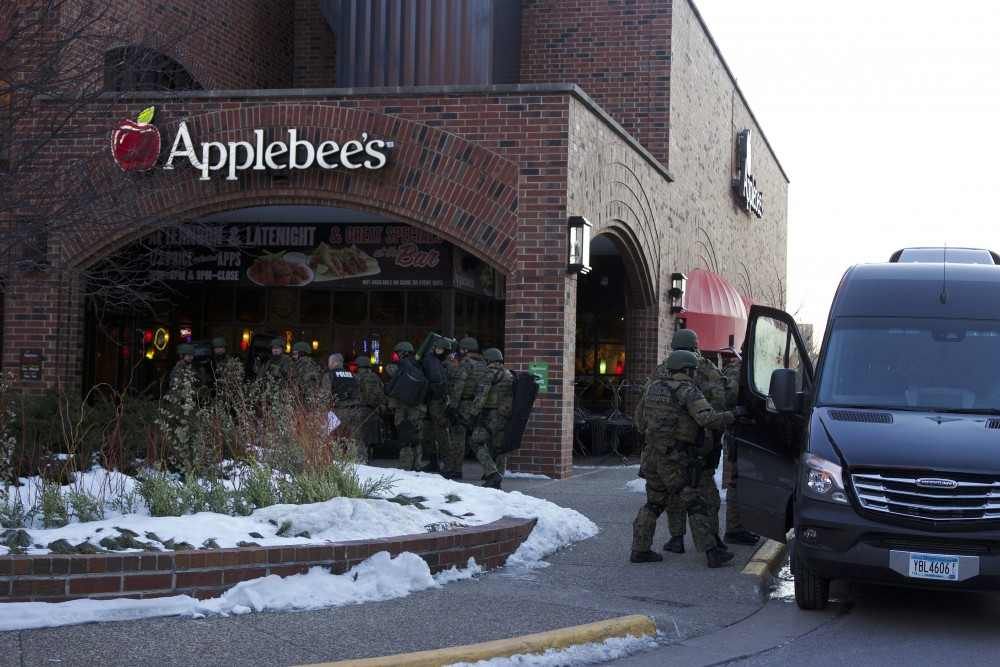 SWAT personnel gather outside the Graduate Hotel early Monday morning in response to what the University is calling a
