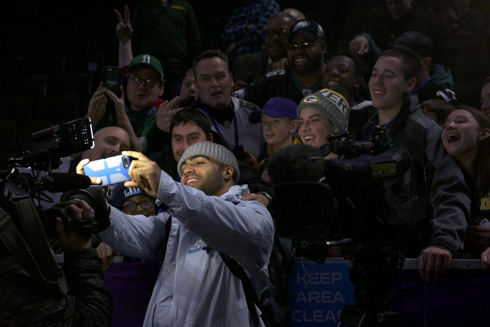 Philadelphia Eagles linebacker Mychal Kendricks takes a selfie with a group of fans during the Super Bowl LII Opening Night event at the Xcel Energy Center on Monday.