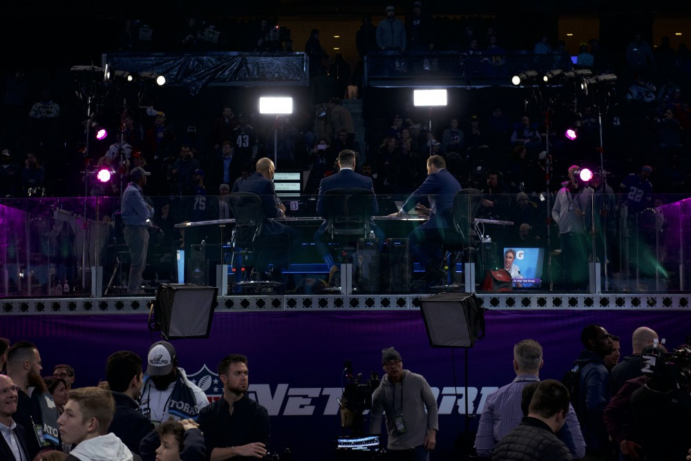 NFL commentators await their cue while members of the media traverse the floor of the Xcel Energy Center to meet with players from the Philadelphia Eagles for the Super Bowl LII Opening Night event on Monday night.