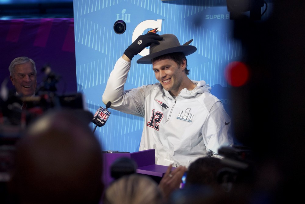 New England Patriots quarterback Tom Brady tries on a hat passed to him by actor J.B. Smoove during the Super Bowl LII Opening Night event at the Xcel Energy Center on Monday.