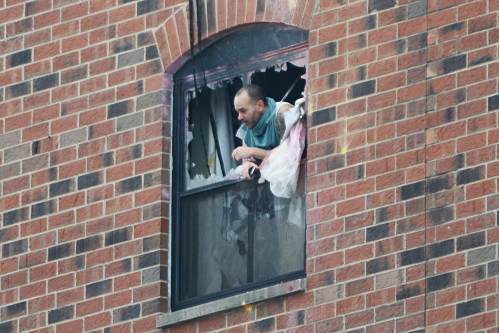 <p>Rashad Bowman, 43, pokes his head out the sixth floor window at 11:40 a.m. Tuesday after police fired gas into a sixth floor room at the Graduate Hotel.</p>