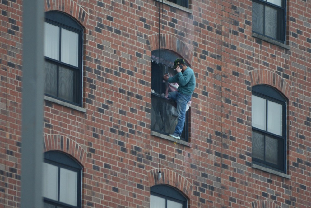 A man sits on the ledge of the sixth-floor window at 1:15 p.m. after two loud explosions were heard at 1:09 p.m. Police say the suspect is in the room and believe he is the only person in the room.