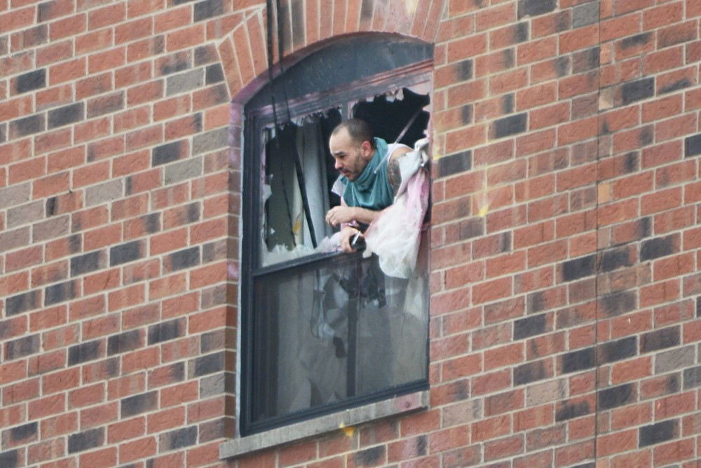 <p>Rashad Bowman, 46, pokes his head out the sixth floor window at 11:40 a.m. after police fired gas into a room at the Graduate Hotel.</p>