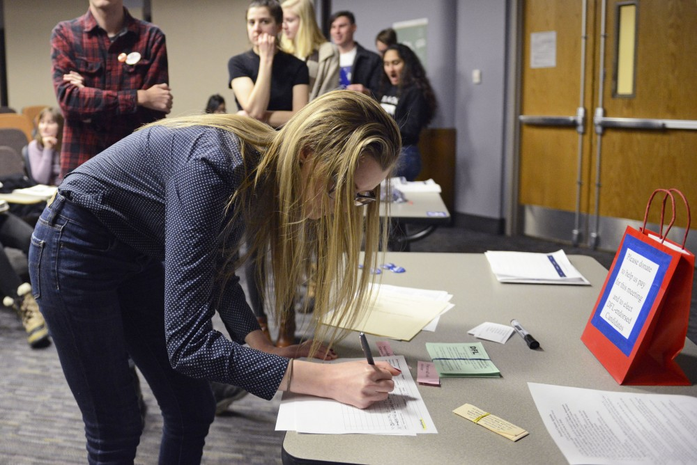 <p>Political science freshman Katie Szarkowicz signs up to be a delegate at the state convention during the DFL Caucus on Tuesday, Feb. 6 in Murphy Hall. Szarkowicz said she attended the caucus because she thinks democracy and being engaged in one's community are important.</p>