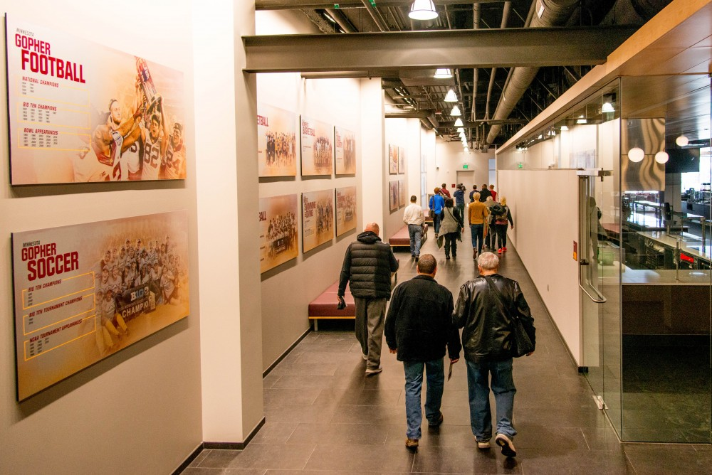 Visitors walk to the Nutrition Center dining area in Athletes Village Saturday, Feb. 10.