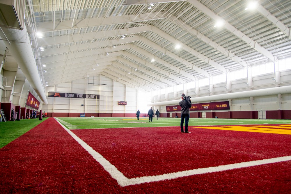 Visitors and media stand on the new football practice filed in Athletes Village on Saturday, Feb 10. The facility has boasted more natural light than most indoor facilities.