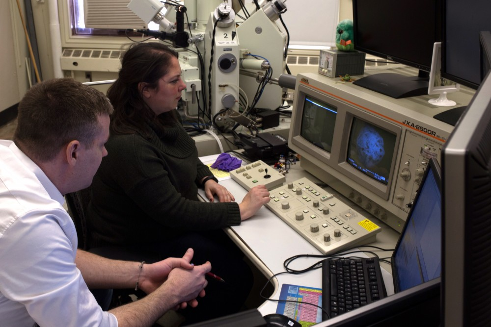 Lab manager Anette von der Handt and local scientist Scott Peterson look at images of micrometeorites through a electron microprobe at the University of Minnesota on Wednesday to identify tiny samples of meteorites he has collected.