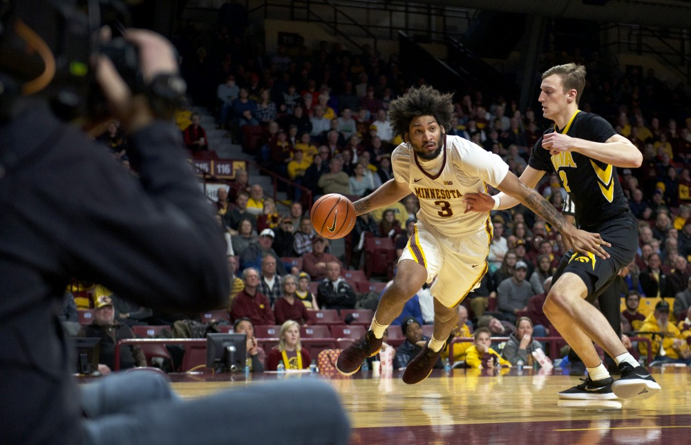 <p>The camera follows forward Jordan Murphy as he maneuvers past Iowa forward Jack Nunge during a game at Williams Arena on Wednesday, Feb. 21.</p>