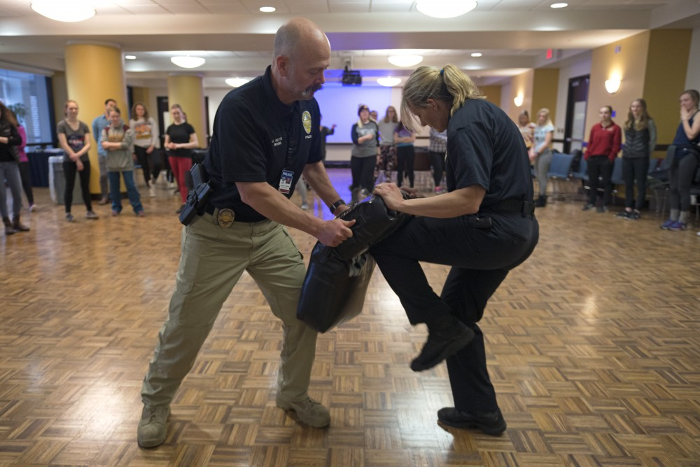 UMPD officers Josh Betts, left, and Lara Bauer demonstrate knee attacks during the self defense workshop in Coffman Union on Saturday, Feb. 24.