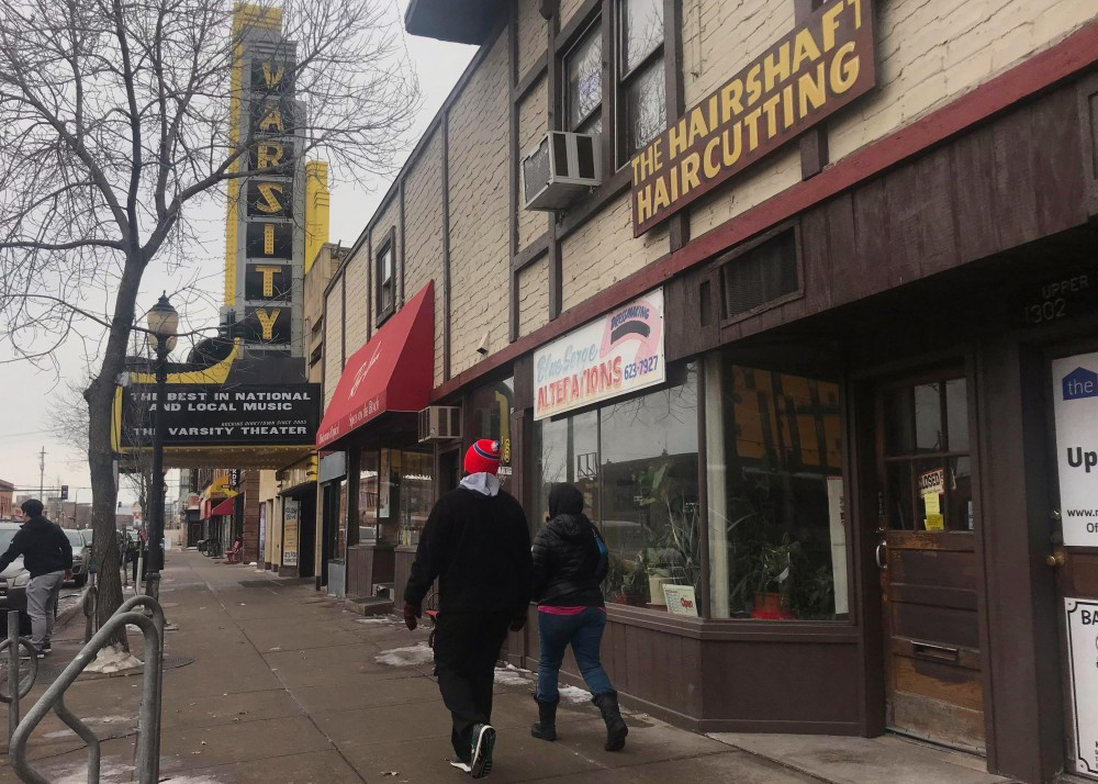People walk past businesses on 4th Street Southeast in Dinkytown on Sunday, Feb. 18. A group of businesses are being forced to close after the buildings owner decided to sell the property.