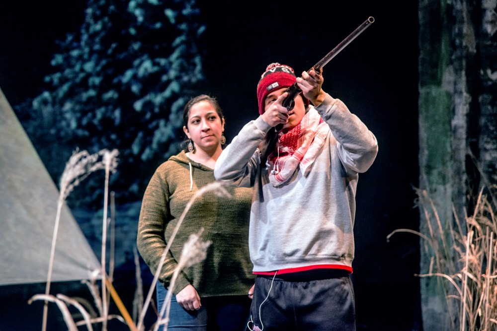Actor Ajuawak Kapashesit fires a prop rifle, while Marisa Carr stands behind him during a tech rehearsal at the Southern Theater on Tuesday, March 6. Almighty Voice and His Wife will open at the Southern Theater on Friday, March 9.