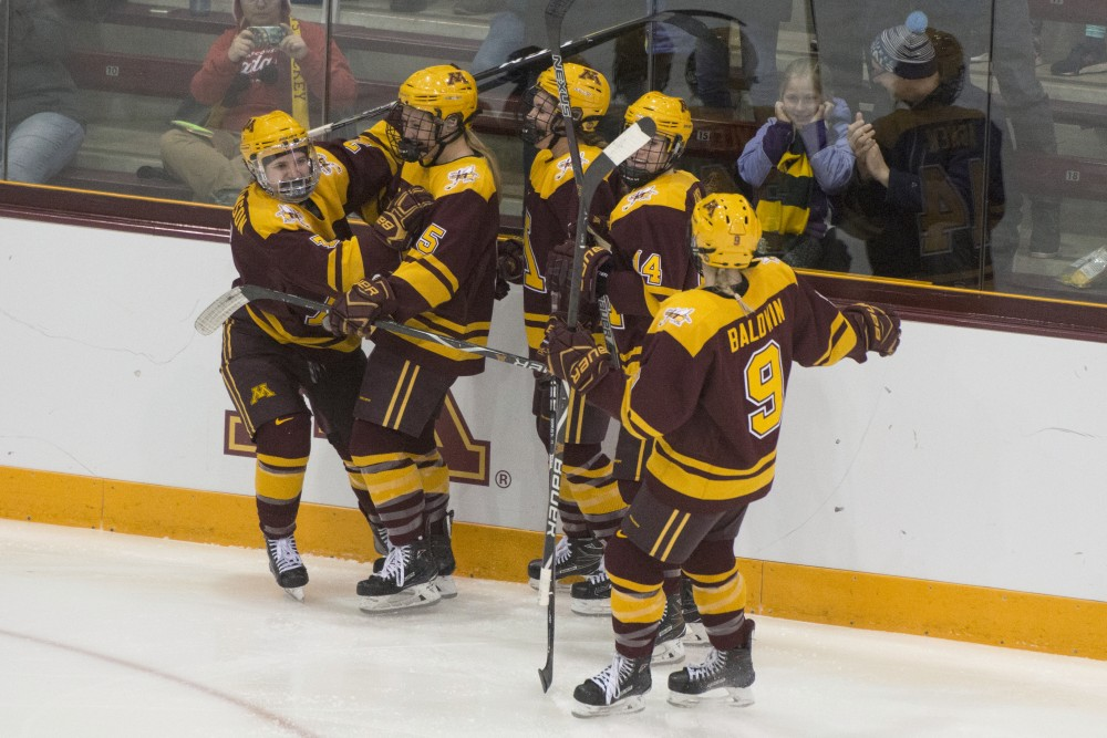 Forward Taylor Williamson, left, celebrates with teammates after scoring a goal during the 2018 WCHA Final on March 4, 2018.