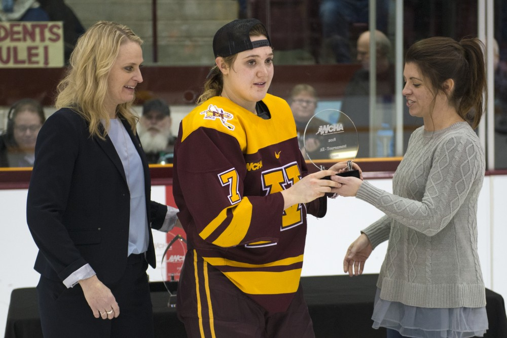 Forward Taylor Williamson receives a trophy after the gophers won the 2018 WCHA Final on March 4, 2018.