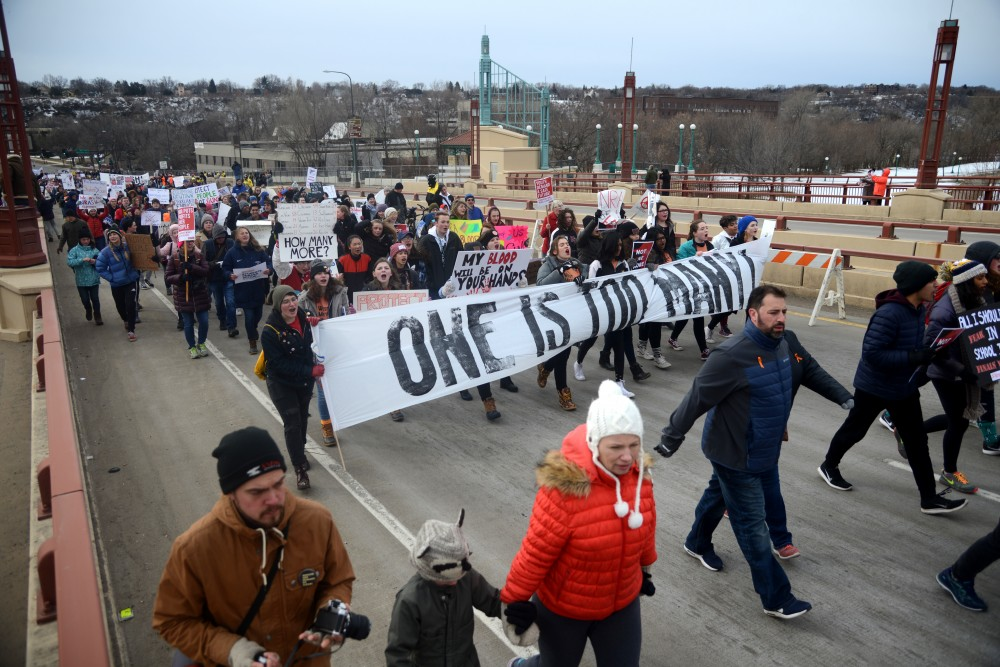 Gun control advocates cross the Wabasha Street South bridge on their march to the State Capitol as part of March for Our Lives Minnesota on Saturday, March 24.