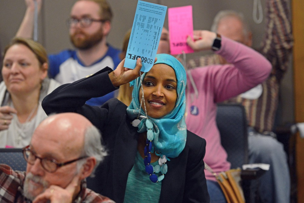 State Rep. Ilhan Omar, DFL-Minneapolis, holds up her credentials to vote on who should be the chair of Senate District 60 during the DFL convention at Edison High School in northeast Minneapolis on Saturday, March 24.