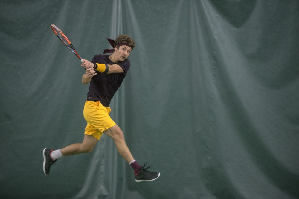 Sophomore Stefan Milicevic returns the ball during a match against Ohio State University at Baseline Tennis Center on Friday, March 30.