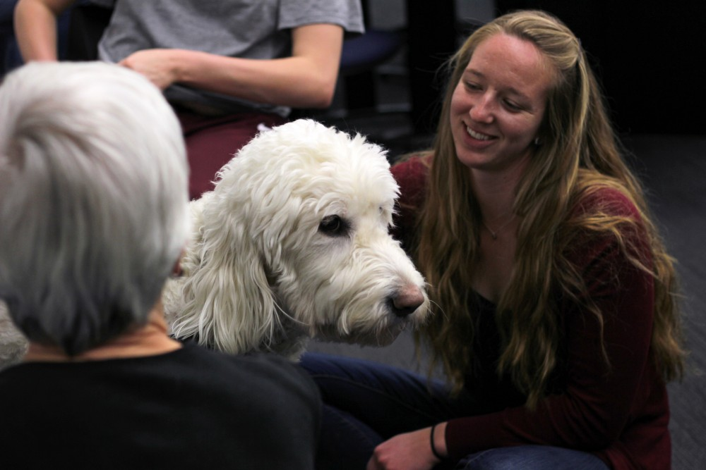 Junior Melissa Foster interacts with the dogs brought in from PAWS before her test in BIOL 1003 on Monday, April 2. She said the dogs helped reduce her stress.