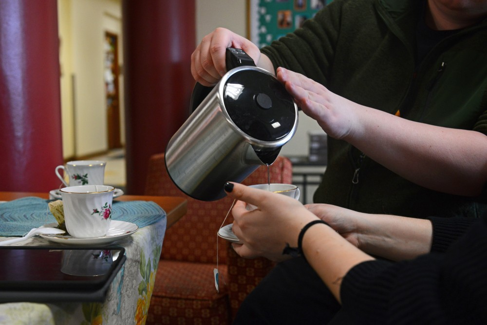 Zachariah Little pours tea for Lauren Foley during a meeting of his tea club in Comstock Hall on Wednesday, April 11.