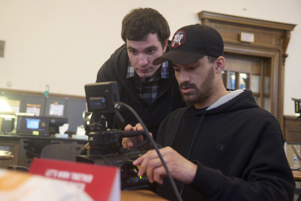 Junior Forrest Casey sets up the nest shot with camera man Reece Bonneville in Walter Library on Saturday, April 21.
