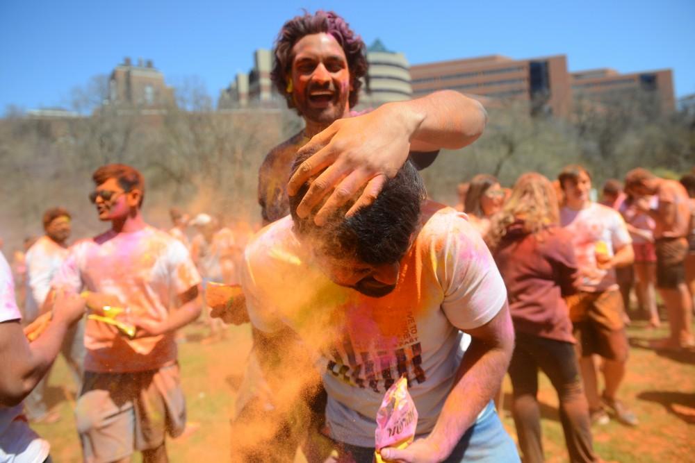 Satish Uppaluri throws color into Rahul Sharan hair at the Holi Festival at East River Flats Park on Sunday, April 29.