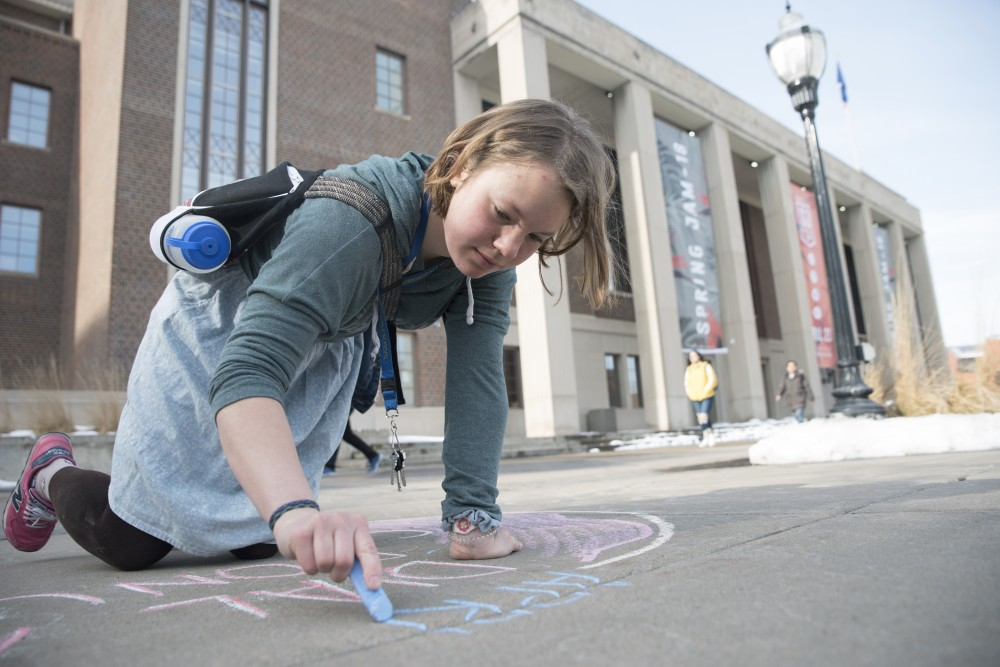 Alice Wilsman draws an advertisement for Dial A Donut with chalk outside of Coffman Union.