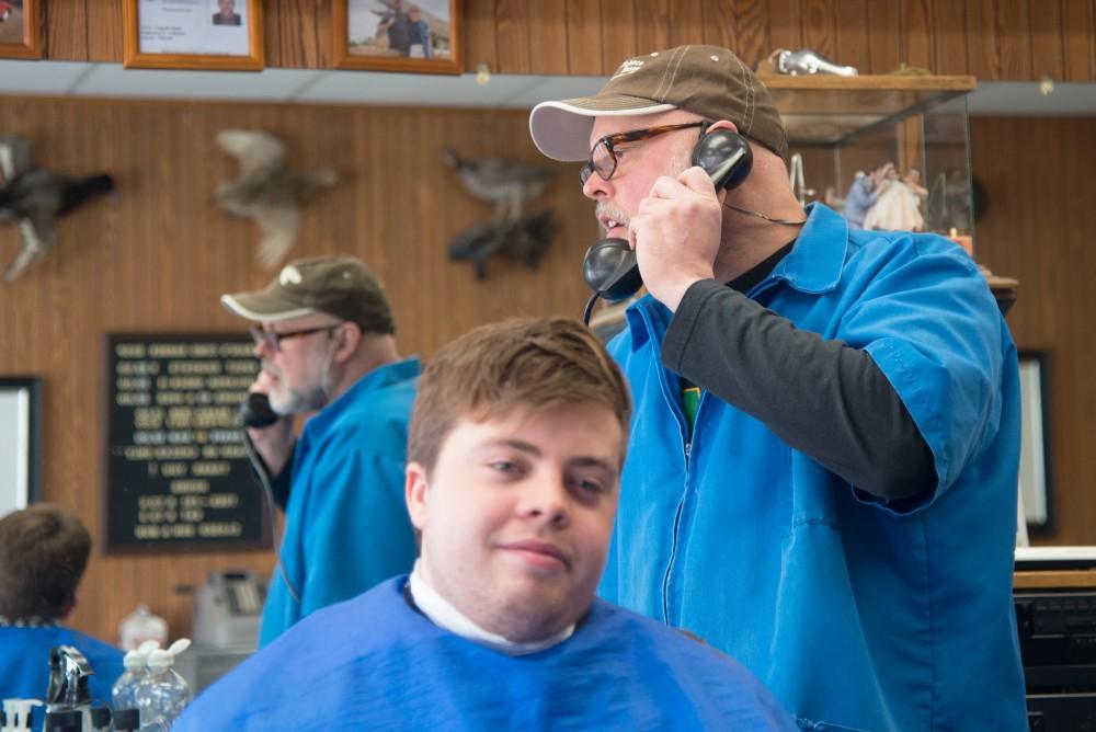 Craig Ylitalo takes a break from cutting Dillon Ronan's hair to answer the phone at Craig's Como Barber Shop.
