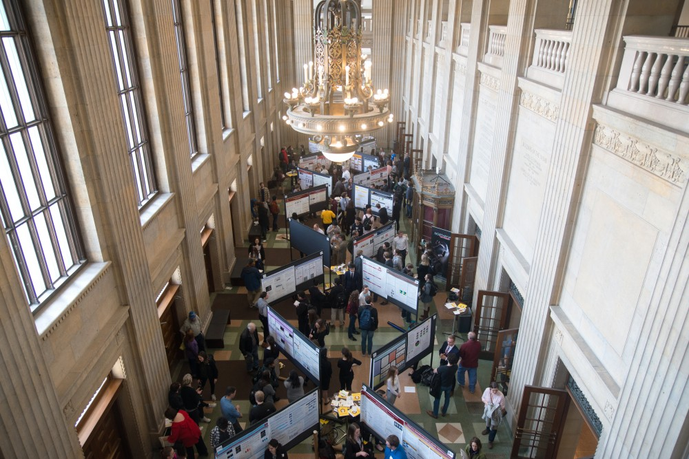Students present their research to the public and mingle during the Undergraduate Research Symposium in Northrop Auditorium's lobby.