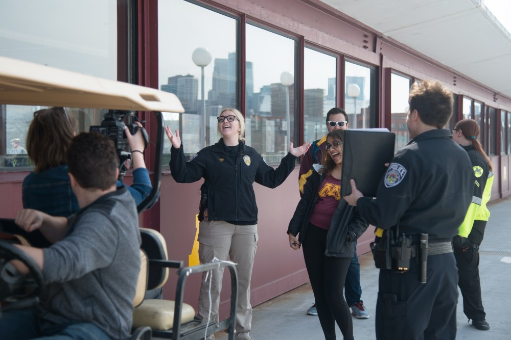 Officer Ashlee Lange, center left, prepares to act as StudioU members and the UMPD Community Engagement Team record updated safety videos for incoming students on the Washington Avenue Bridge.
