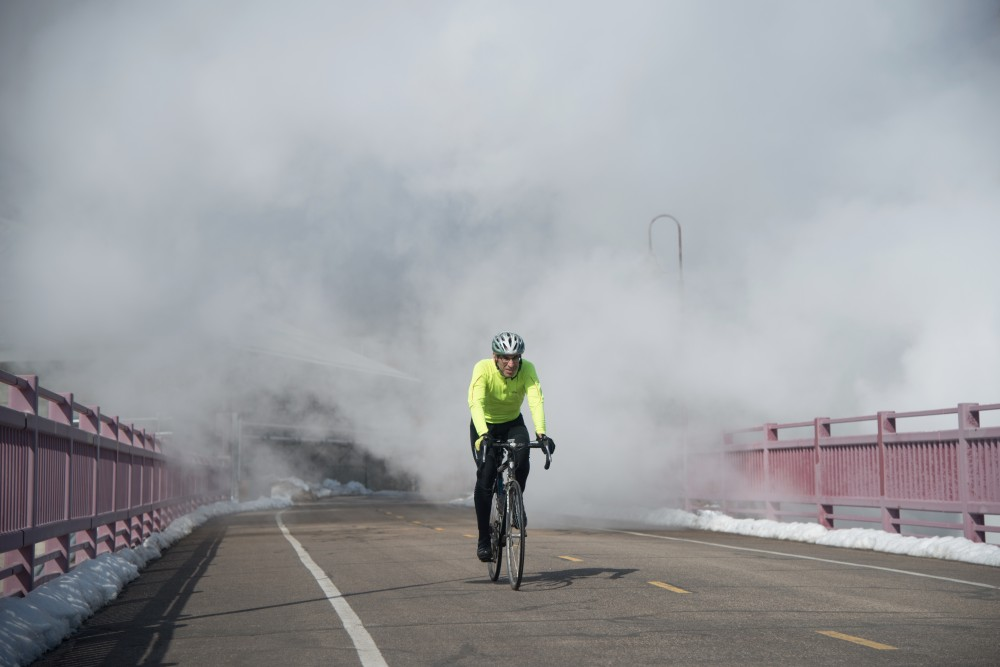 A bicyclist emerges from a cloud of steam on Northern Pacific Bridge #9 near the Education Sciences Building.