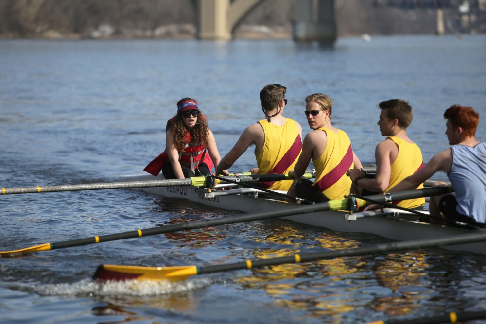 The University of Minnesota club men's rowing team backs into the docks on the Mississippi River.