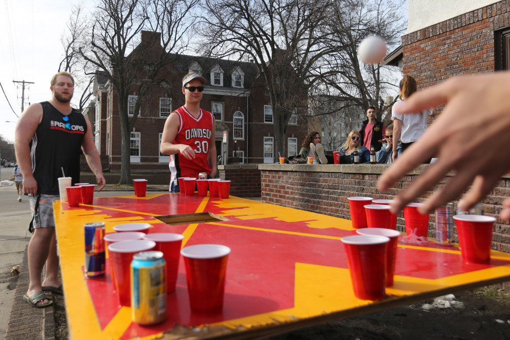 Zach Kosel and Dan Davidson watch to see if they make the cup during a beer pong game outside their fraternity.