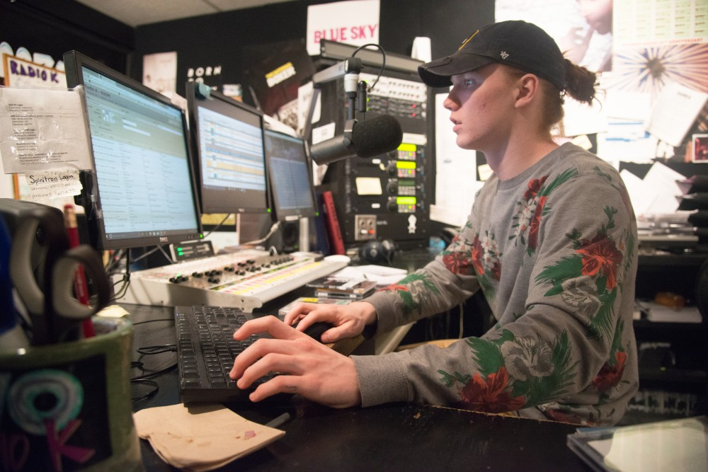 Will Cushman, a freshman journalism student enters song information into the computer during his variety shift at Radio K.