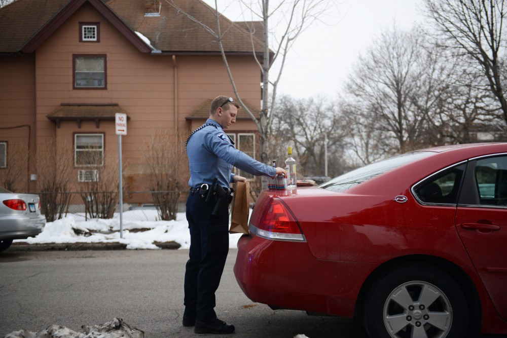 A police officer bags up alcohol found in a vehicle during a traffic stop in Dinkytown.