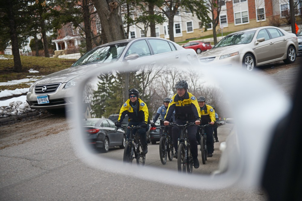 A group of eight police officers patrol on bikes through Dinkytown.