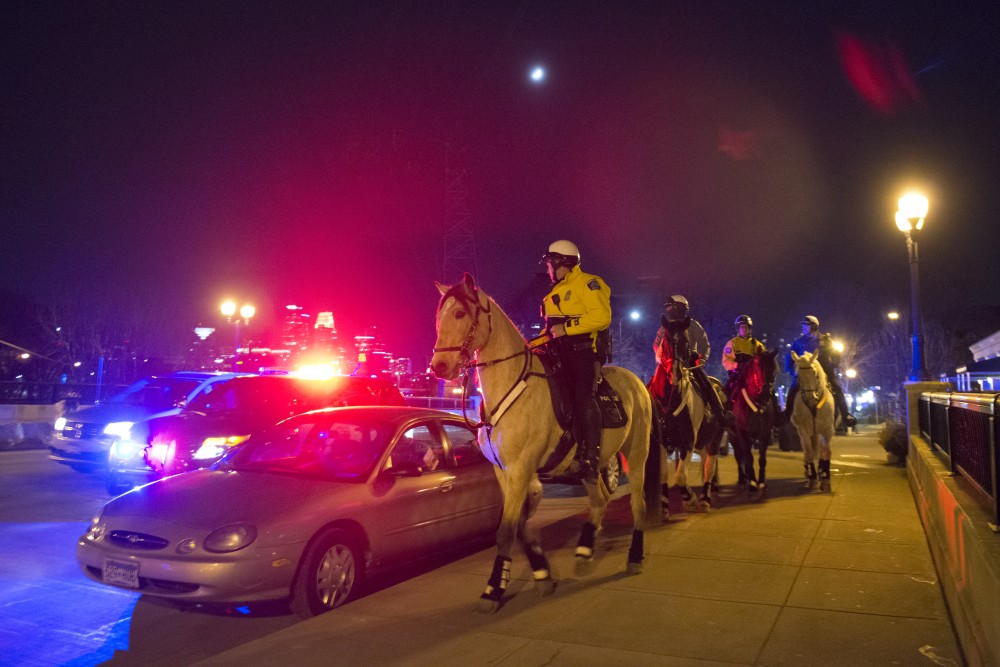 Four police officers on horses patrol through Dinkytown.