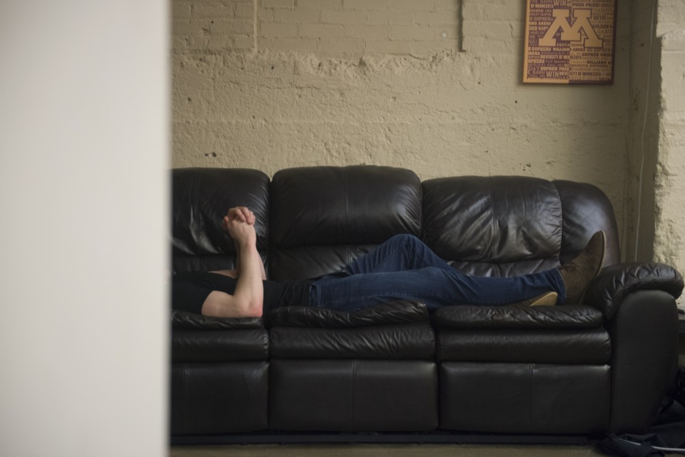 A student falls asleep on the couch after bar close in Como.