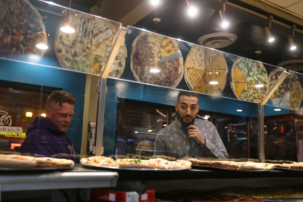 Andre Jones and Cole Rice decide what slice to buy at Mesa Pizza in Dinkytown.